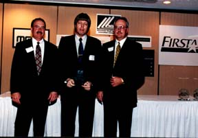 Dan Schramm receives an award from the Wisconsin Small Business Innovation Consortium in Madison, WI during 1998.